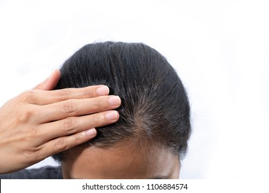 Young woman shows her gray hair roots isolated on white background