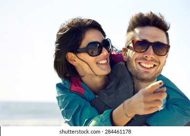 Young woman shows her man the Sea View, Happy couple having fun on summer sea
