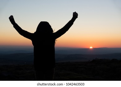 A young woman shows joyous gestures in the setting sun of Dartmoor, United Kingdom.