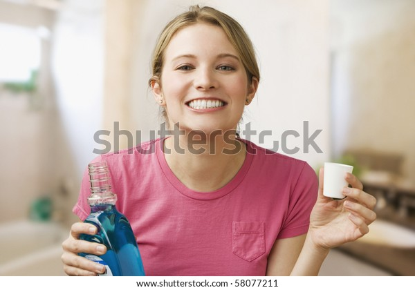 A young woman shows off her teeth while holding a bottle of mouthwash.  Horizontal shot.