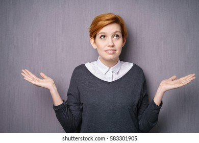 Young woman shrugging her shoulders and looking up into the air indicating she neither knows nor cares