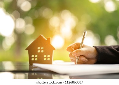 Young woman signing banking Loan Contract for buying a new house from real estate agent, installment payment by monthly basis as planning for long term contract. Dreaming to become owner residence.