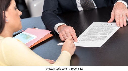 Young woman signing contract with financial adviser