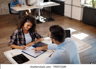Young woman signing contract with manager