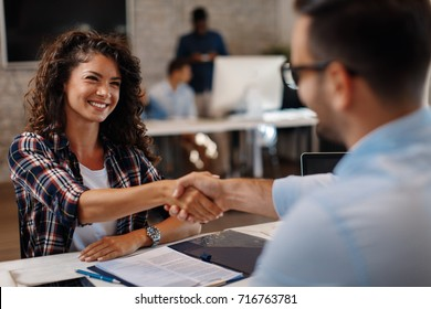 Young woman signing contracts and handshake with a manager