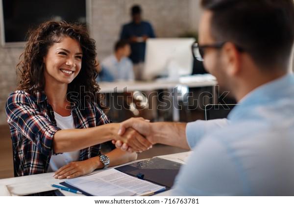 Jeune femme signant des contrats et serrant la main avec un responsable