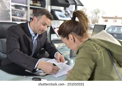 Young woman signing credit contrat for car purchase