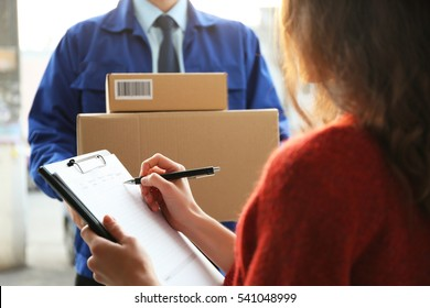 Young woman signing documents after receiving parcels from courier, closeup