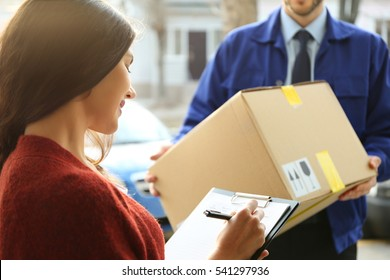 Young woman signing documents after receiving parcel from courier, closeup