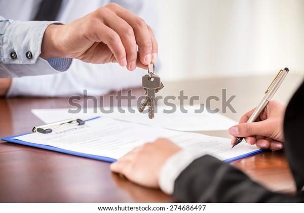 Junge Frau unterzeichnet einen Finanzvertrag mit männlichen Immobilienmaklern. Nahaufnahme.