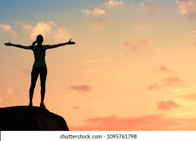 Young woman silhouette against sunset with arms up in sky feeling free and happy. Freedom, and joy concept.