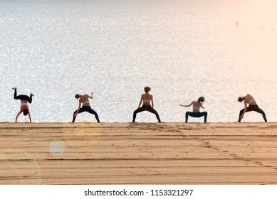 Young woman silhouette doing workout on the beach at dawn