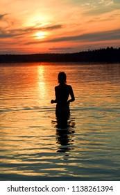 Young woman silhouette at Krasavitsa lake, Zelenogorsk, Russia