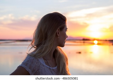 Young woman silhouette at sunset on lake