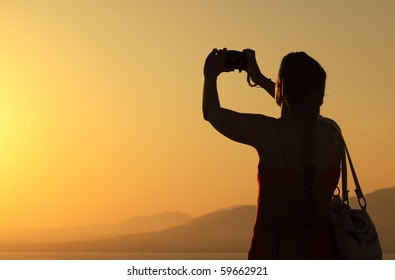 Young woman silhouette taking photos about landscape outdoor
