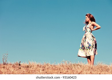 young woman in silk dress stand on hill in dry grass with clear blue sky in background, grain added