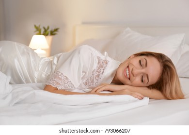 Young woman in silk robe sleeping on bed at home