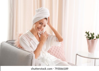 Young woman in silk robe and towel resting at home
