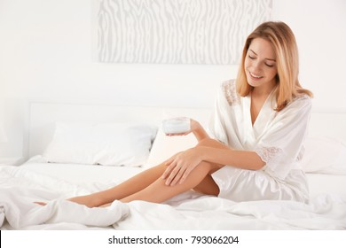 Young woman in silk robe using cosmetic product at home