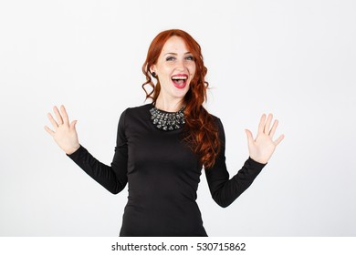 Young woman singing and dancing, white background. In black classic clothes