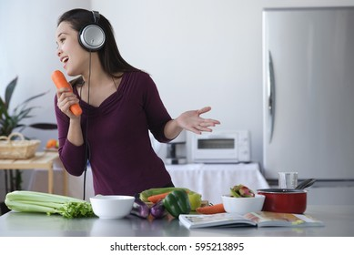 Young woman singing into carrot