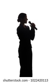 Young woman singing into the microphone, raising his hands - silhouette