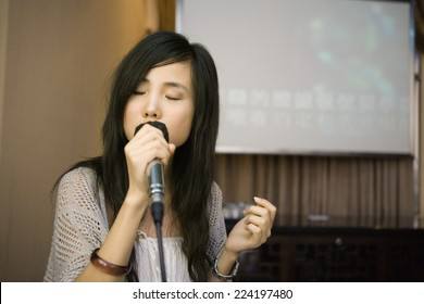 Young woman singing karaoke, eyes closed