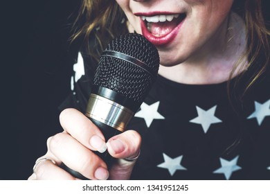Young woman singing a song with a microphone