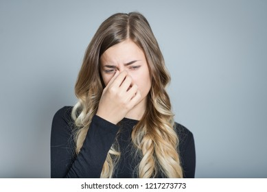 Young woman with sinus pressure pain, isolated over gray background