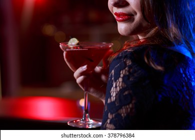 Young woman sipping red sweet drink in bar