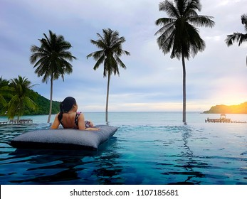 Young woman sit in beanbag relaxing on the swimming pool and looking forward, near the sea in the sunset