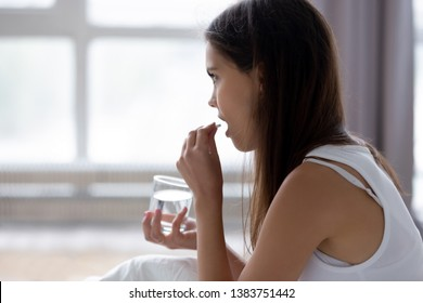 Young woman sit in bed feeling unwell holding glass of water taking medicine after wake up, millennial girl have medication painkiller suffer from morning sickness or headache. Health problem concept