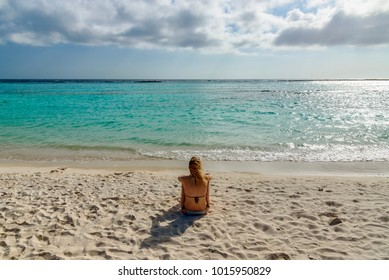 A young woman sit on the beautiful Baby Beach in Aruba.