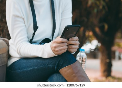 Young woman sit on the chair and using smart phone while on vacation at the national park. Adventure travel concept