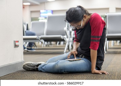 A young woman sit on floor and recharges the phone from the wall socket in the hall. Passengers relaxed in the waiting room at the airport. Girl with mobile phone in the lobby.