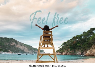 """Young woman sit on a lifeguard chair at the beach on summer holidays, at Catalonia, Costa Brava, Spain. Open arms to the sky with the words """"feel free"""" write on it. Natural landscape."""