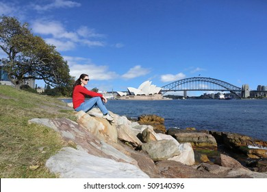 Young woman sit on a rock and looks at Sydny Harbour landscape during sunrise in Sydney New South Wales, Australia.