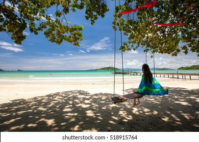 Young woman sit on rope swing on the beach