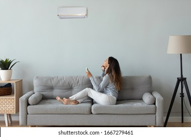 Young woman sit relax on cozy sofa at home turn on air conditioner breathing fresh air indoors, happy millennial girl rest on comfortable couch under condition device in cozy living room
