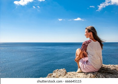 Young woman siting on the stone, looking at sea