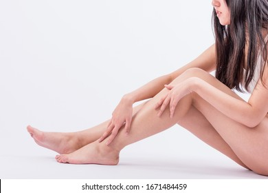 Young woman siting on white and touching leg by hands. Beauty of woman with perfect legs
