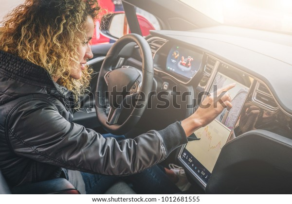 Young woman sits behind wheel in car and uses an electronic dashboard, tablet computer. Girl is traveler looking for a way through navigation system. Trip, caravanning, tourism, journey.