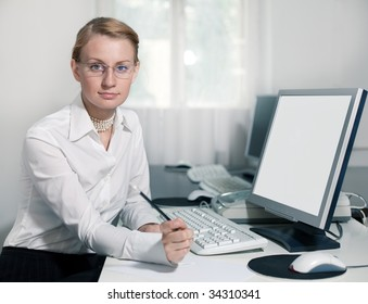 Young woman sits by computer and looks at camera