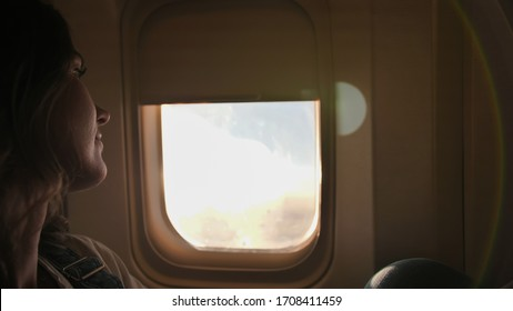 A young woman sits by the window in the cabin at dusk.