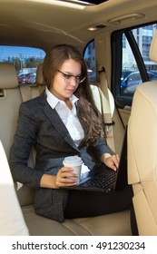 Young woman sits in the car and works at the laptop