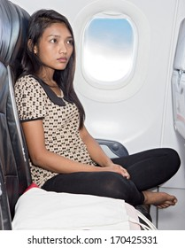Young woman sits in a chair of the airplane. Tourist flying on an airplane next to a window with a blue sky. Woman traveling aircraft. Flying a plane with an Asian passenger.