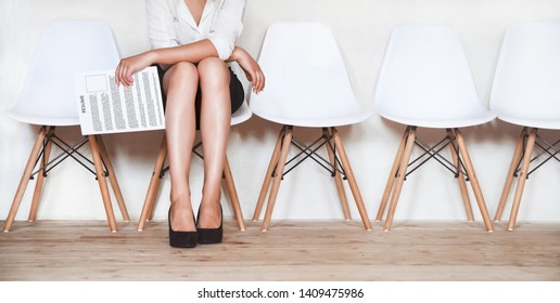 A young woman sits in a chair with a resume in her hands in anticipation of an interview.
