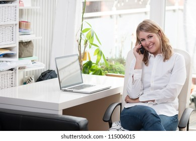 Young woman sits at the desk with a notebook and phones