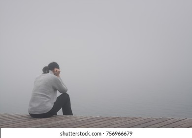 Young woman sits lonely at the edge of a wooden path of a bridge bent and sadly lost in thought in the fog