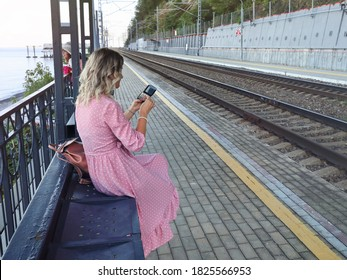 Young woman sits on bench of railway platform, waiting for her train and at this time wants to correct her makeup, looking in pocket mirror